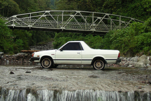 Subaru Brat in a Brook with a Bridge Featured in Background