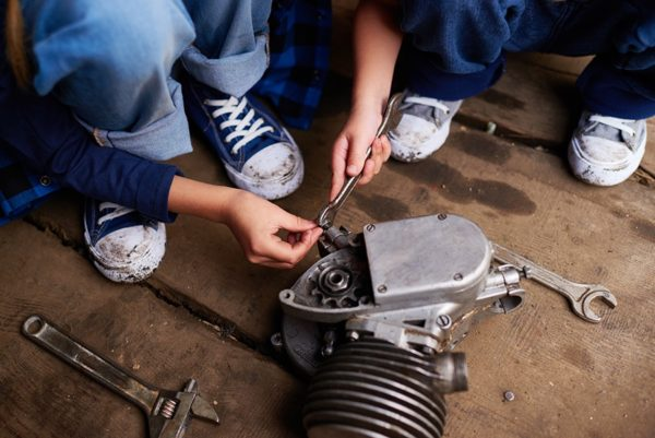 Two mechanics working on car part