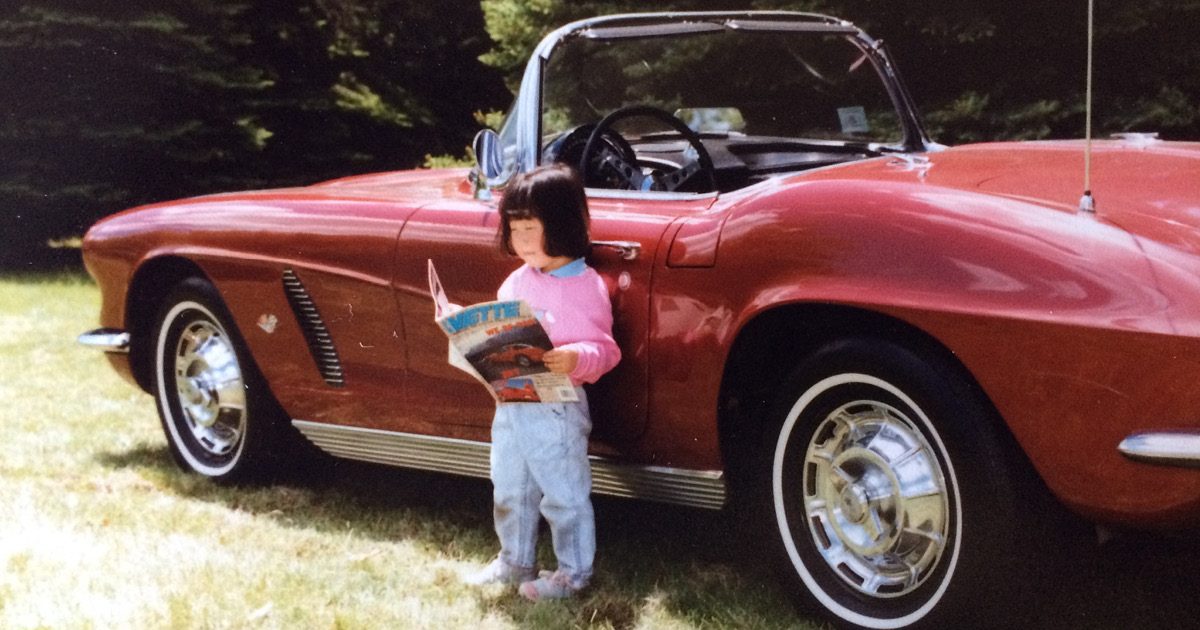 young girl next to vintage classic corvette