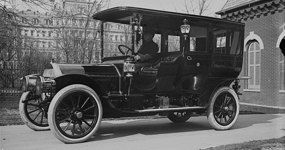 President Taft's first presidential automobile purchase, the Pierce-Arrow, which he bought in 1909. In this photo, a chauffeur sits in the car parked outside of the White House garage that same year.