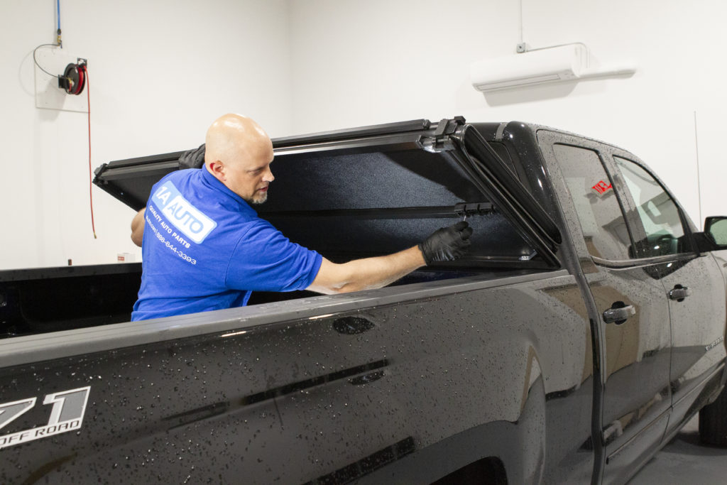 1A Auto Mechanic Andy installs a Trail Ridge tonneau cover on a truck in our R&D center.