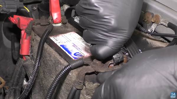 Check your battery's connections, as our mechanic does in this photo.