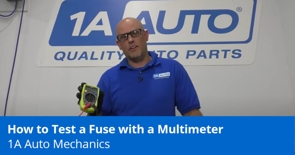 Mechanic testing fuse with multimeter