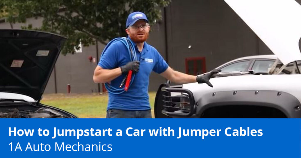 Mechanic showing how to jumpstart a car with jumper cables