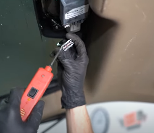 Testing a rear wiper electrical connector with a test light on the 4th gen Ford Explorer