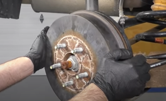 Turning a rear brake drum to test for resistance and the adjustment