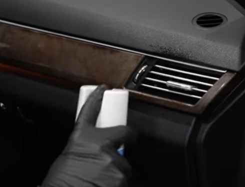 Using disinfectant spray on a car vent