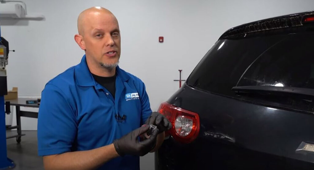 Mechanic showing how to reattach car emblem
