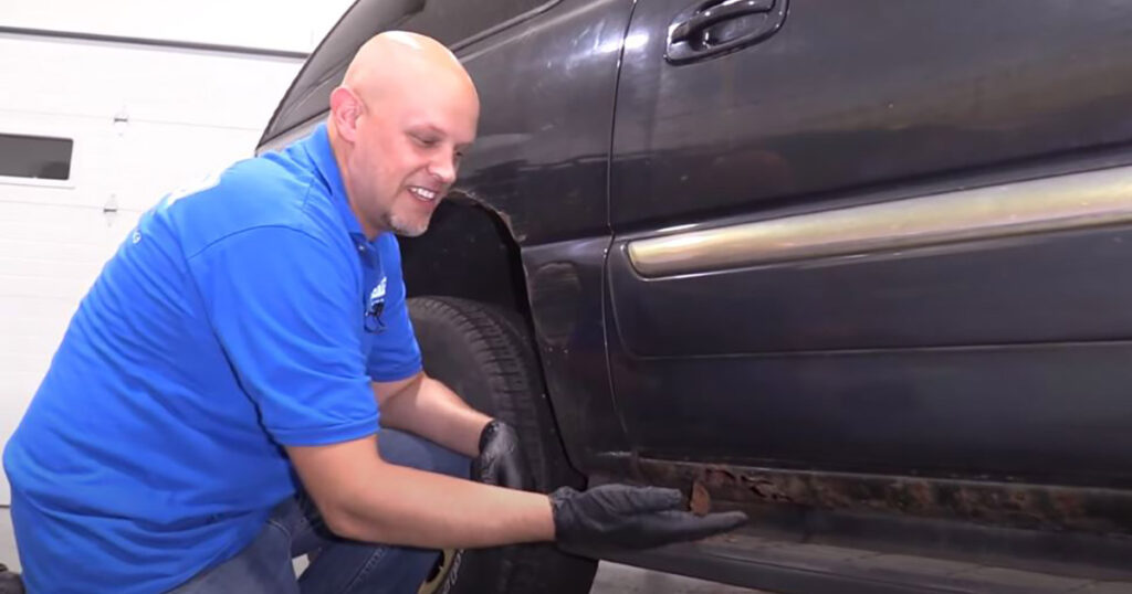 Mechanic showing rusted rocker