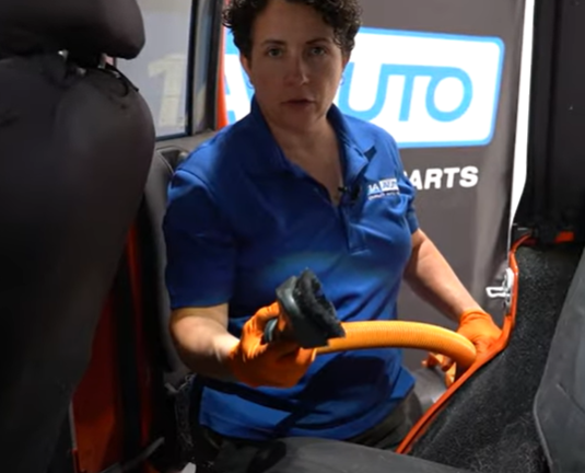 Removing dog hair from a car seat with a vacuum